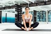 Atraktivní mladá žena, táhnoucí se v tělocvičně na fitness mat