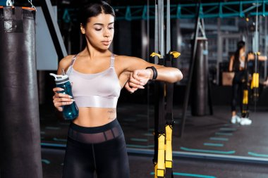 Fantastic sportive girl holding water bottle while looking at fitness tracker in sports gym
