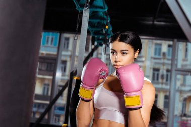 Attractive strong girl in protective gloves practicing boxing in gym