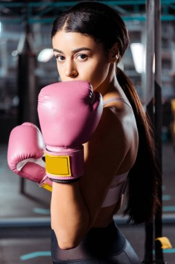 Attractive sportive girl in boxing box gloves in sports gym