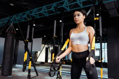 Beautiful sportive girl exercising with resistance bands in fitness gym