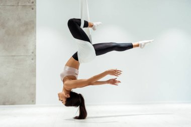 Beautiful relaxed girl practicing antigravity yoga in inversion position in studio