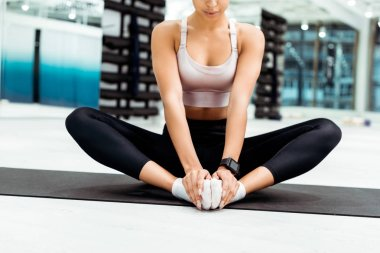Partial view of young woman stretching in gym