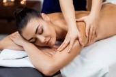 attraktive junge Frau mit geschlossenen Augen bei einer Massage im Wellnessbereich