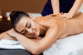 attractive smiling young woman with closed eyes enjoying massage in spa