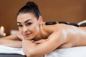 krásná mladá žena se těší masáž lávovými kameny a usmívá se na kameru ve spa salonu