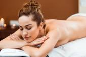 Fotografie atraktivní mladá žena se zavřenýma očima, ležící na lehátku ve spa salonu