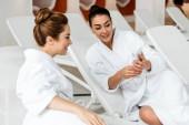 Fotografia giovani donne felici che esaminano smartphone mentre insieme sdraiati sui lettini nella spa