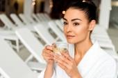 Fotografia attraente giovane donna in accappatoio bere tisane e distoglie lo sguardo nella spa