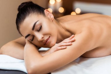attractive smiling young woman with closed eyes lying on massage table in spa