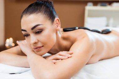 Beautiful young woman lying on massage table and enjoying hot stone massage stock vector