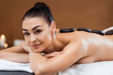 beautiful young woman enjoying hot stone massage and smiling at camera in spa salon