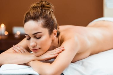 attractive young woman with closed eyes lying on massage table in spa salon
