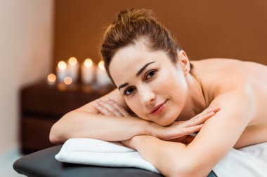 attractive young woman lying on massage table and smiling at camera
