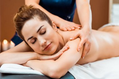 beautiful young woman with closed eyes enjoying massage in spa salon