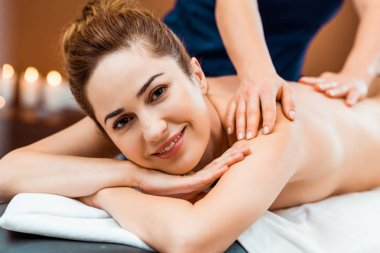 beautiful happy young woman smiling at camera while having massage in spa