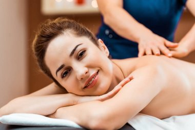 beautiful young woman smiling at camera while having massage in spa