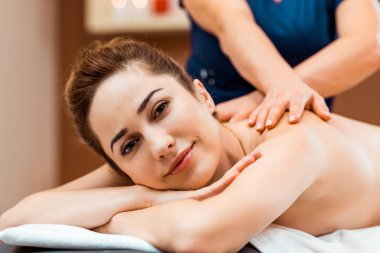 Attractive young woman smiling at camera while having massage in spa stock vector