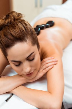 high angle view of beautiful young woman with closed eyes enjoying hot stone massage