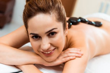 attractive young woman smiling at camera while enjoying hot stone massage