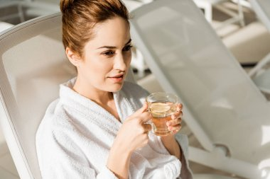 high angle view of young woman holding cup of herbal drink and looking away while resting in spa