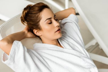 beautiful young woman in bathrobe lying with hands behind head and closed eyes in spa