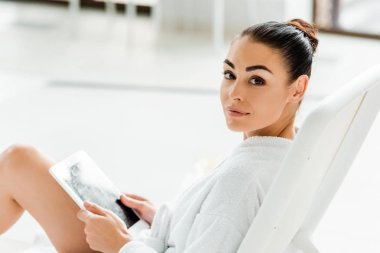 attractive young woman holding digital tablet and looking at camera in spa