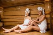 atraktivní mladé ženy se usmívá na kameru při relaxaci společně v sauně