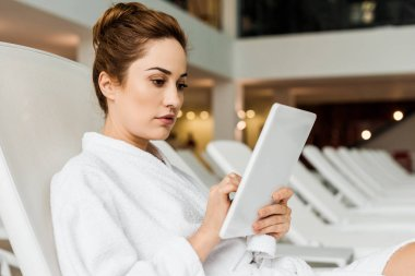 attractive young woman in bathrobe using digital tablet while relaxing in spa