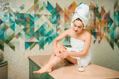 young woman applying scrub while sitting on hammam table in turkish bath