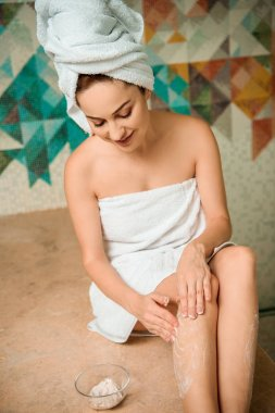 smiling girl applying scrub while sitting on hammam table in turkish bath