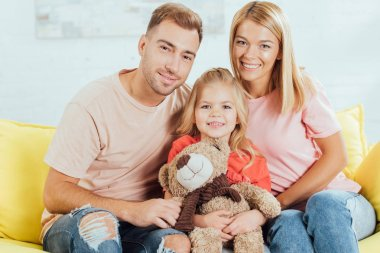 smiling parents sitting on couch, looking at camera and daughter holding teddy bear