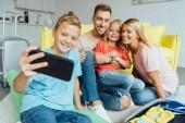 Fényképek boldog családi figyelembe selfie a smartphone, míg a csomagolás, vonatkozó nyaralás