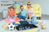 šťastná rodina balení zavazadel pro letní dovolenou, cestování koncepce