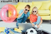 Photo kids in glasses using laptop and packing for family summer holiday, travel concept
