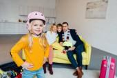 Kind auf Snowboard posiert auf Vordergrund während glückliche Familie großartige Zeit und Verpackung für Winterurlaub