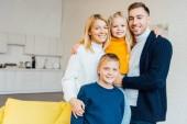 šťastná rodina v neformálním oblečení, objímání a při pohledu na fotoaparát