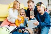 glückliche Familie mit viel Zeit, digitalem Tablet und Verpackung für den Winterurlaub