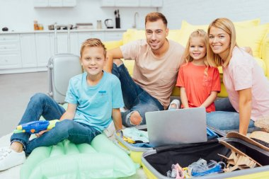 happy family using laptop, planning summer vacation, packing luggage and having great time, travel concept