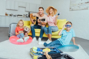 happy family holding passport, packing baggage for summer vacation and having great time, travel concept