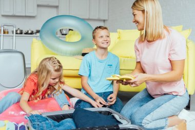 happy family having fun and packing for summer vacation, travel concept