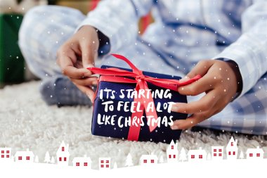 cropped image of african american child in pajamas opening christmas gift on floor with