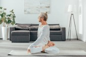flexible athletic man practicing yoga on mat at home