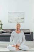 flexibilní dospělý muž přemýšlí v lotosové pozici na jógu doma