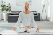 sportovní dospělý muž přemýšlí v lotosové pozici na jógu doma
