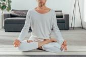 Schnappschuss von Mann in Sportbekleidung, der zu Hause auf Yogamatte meditiert