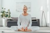 člověk přemýšlí v lotosové pozici na jógu doma