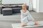 pohled z vysoké úhlu flexibilní koncentrované dospělého člověka cvičit jógu a koukal doma