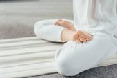 Fotografie Oříznout záběr člověka meditoval v lotosové pozici na jógu doma