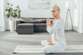 Photo adult man meditating in lotus position and looking at camera at home